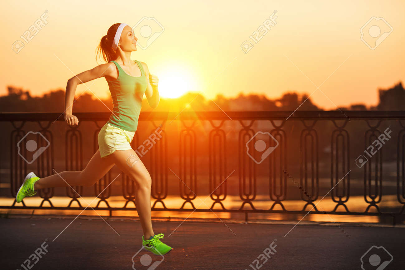 Running woman. Runner is jogging in sunny bright light on sunrise. Female fitness model training outside in the city on a quay. Sport lifestyle. - 32020349