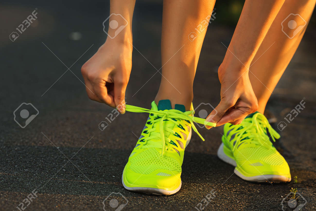 Running shoes. Barefoot running shoes closeup. Female athlete tying laces for jogging on road in minimalistic barefoot running shoes. Runner getting ready for training. Sport lifestyle. - 31878063