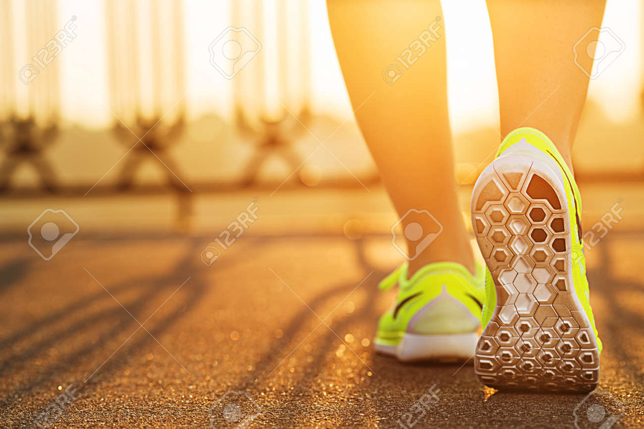 Runner woman feet running on road closeup on shoe. Female fitness model sunrise jog workout. Sports healthy lifestyle concept. - 31878071