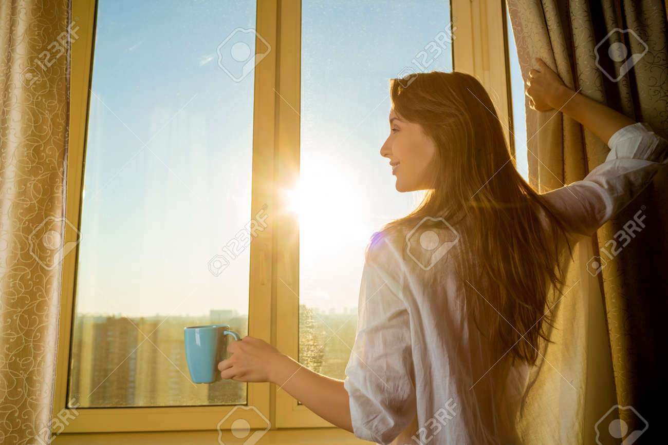 Woman in the morning. Attractive woman with neat body is holding a cup with hot tea or coffee and looking at the sunrise standing near the window in her home and having a perfect cozy morning. - 31878158