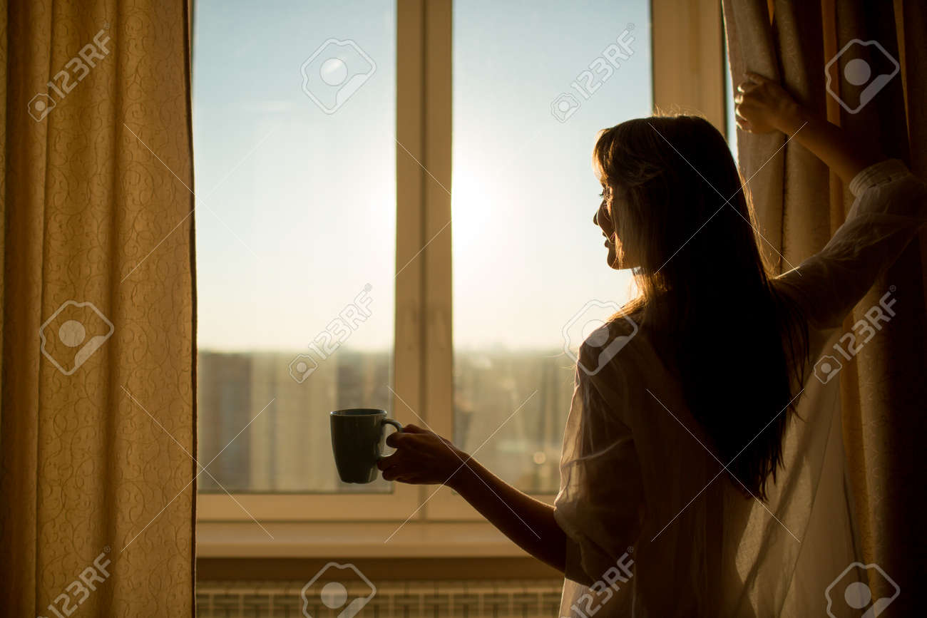 Woman in the morning. Attractive woman with neat body is holding a cup with hot tea or coffee and looking at the sunrise standing near the window in her home and having a perfect cozy morning. - 31878159
