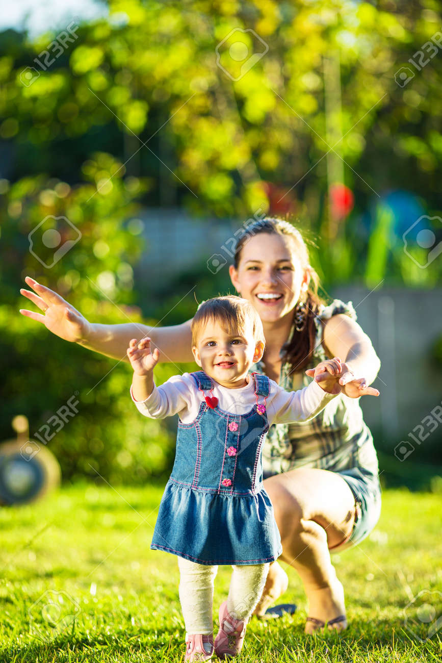 Baby girl is doing her first steps with mothers help. Cute little girl learns to walk with her young mom helping her in the sunny garden outdoors. Happy childhood and motherhood concept. - 32330490