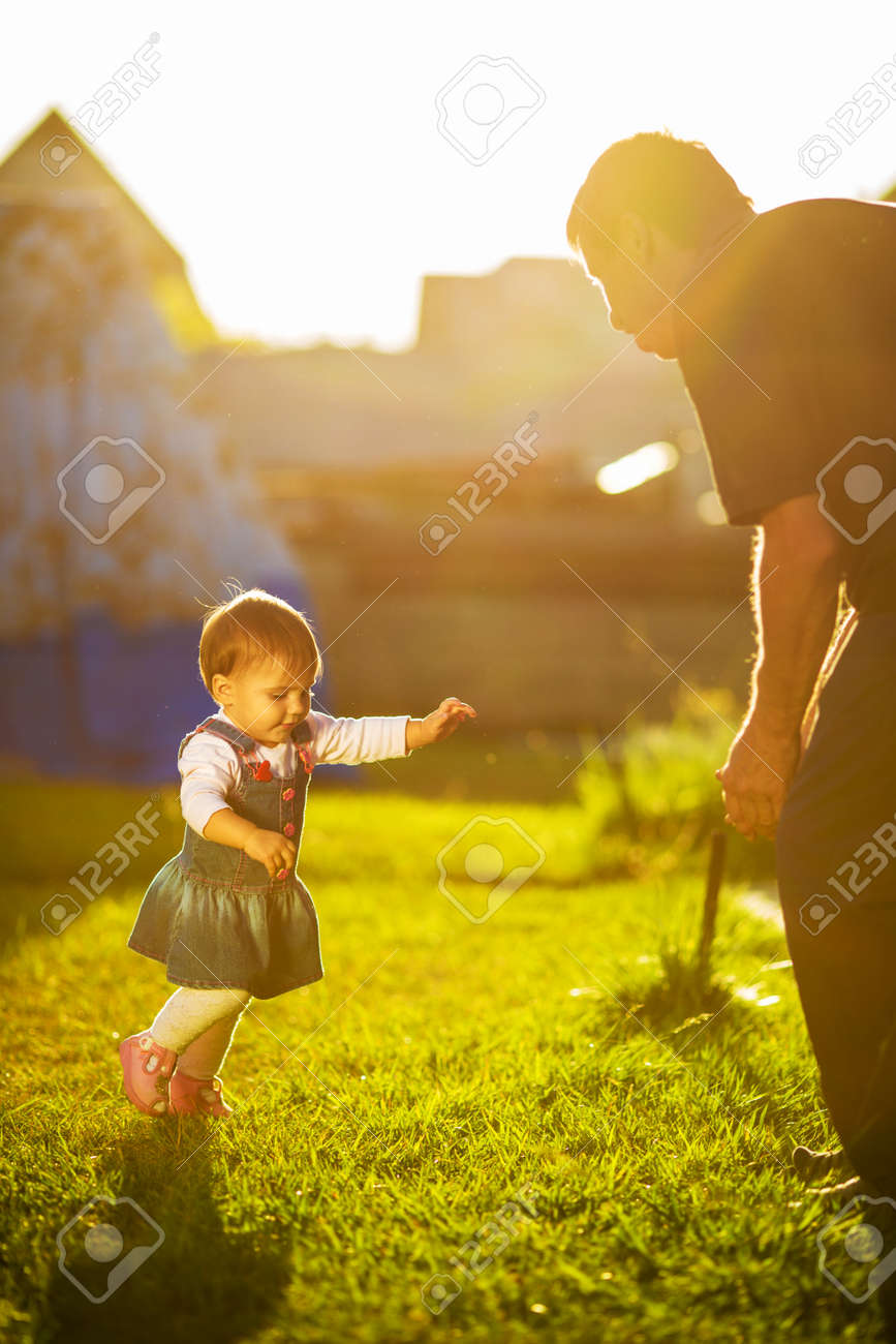 Baby girl is doing her first steps. Cute little girl is learning to walk and going to her grandfather in a sunny garden. Happy childhood concept. - 31878178