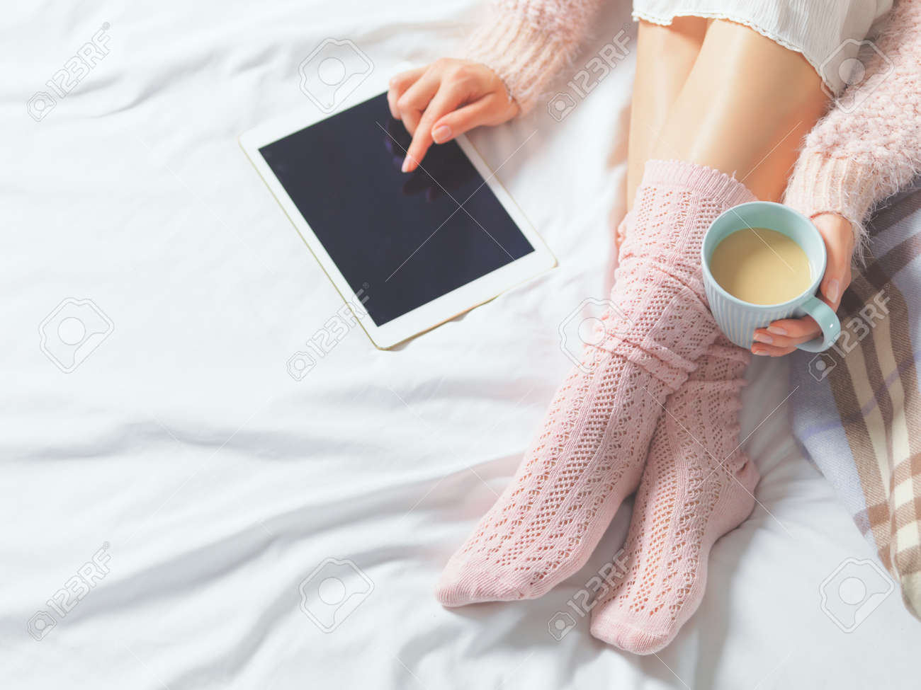 Woman using tablet at cozy home atmosphere on the bed. Young beautiful woman enjoying free time using technological device, holding a cup of cocoa or coffee. Soft light - 41581615