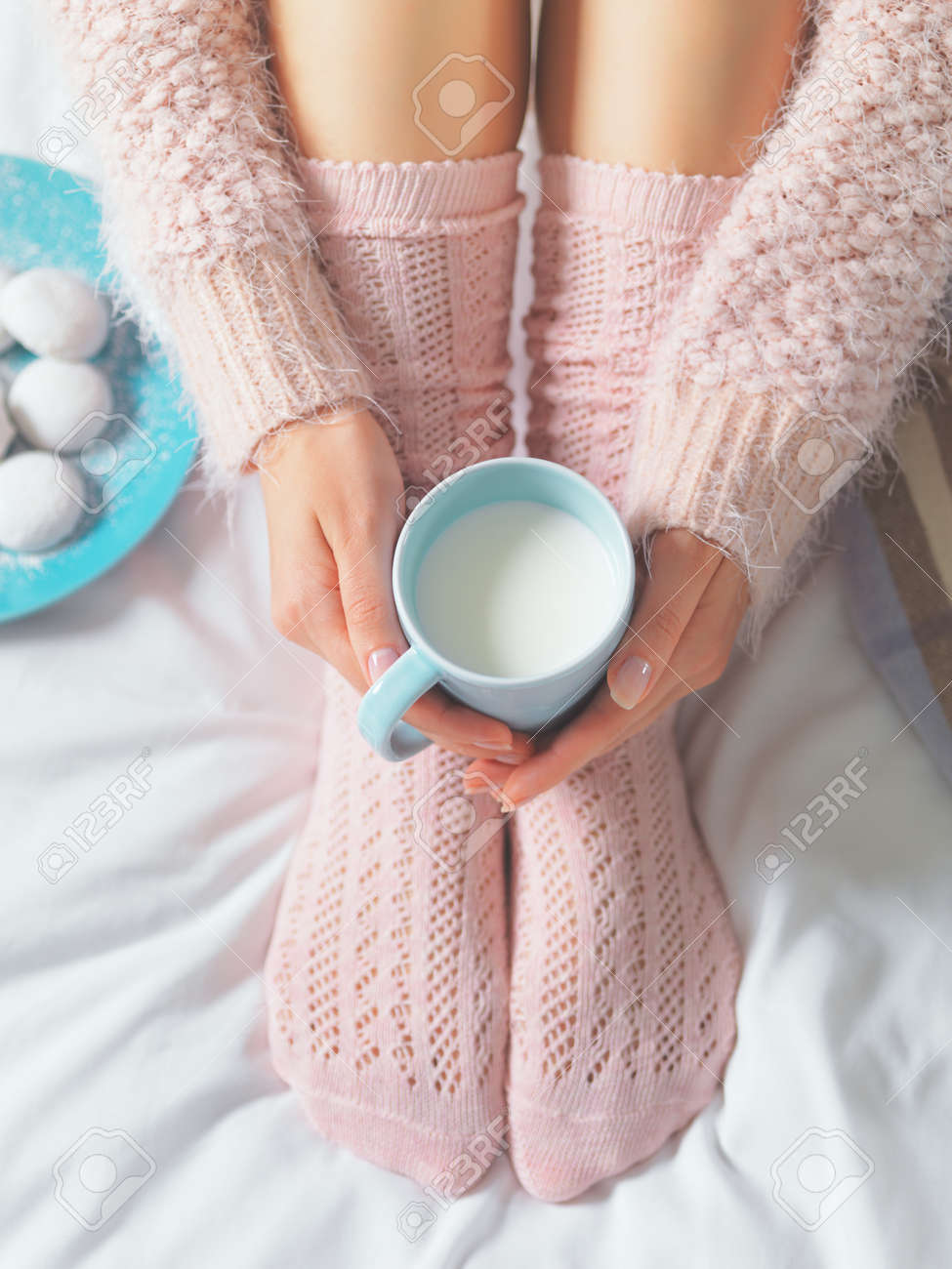 Woman relaxing at cozy home atmosphere on the bed. Young woman with cup of milk in hands and cookies enjoying comfort. Soft light and comfy lifestyle concept. - 41581616