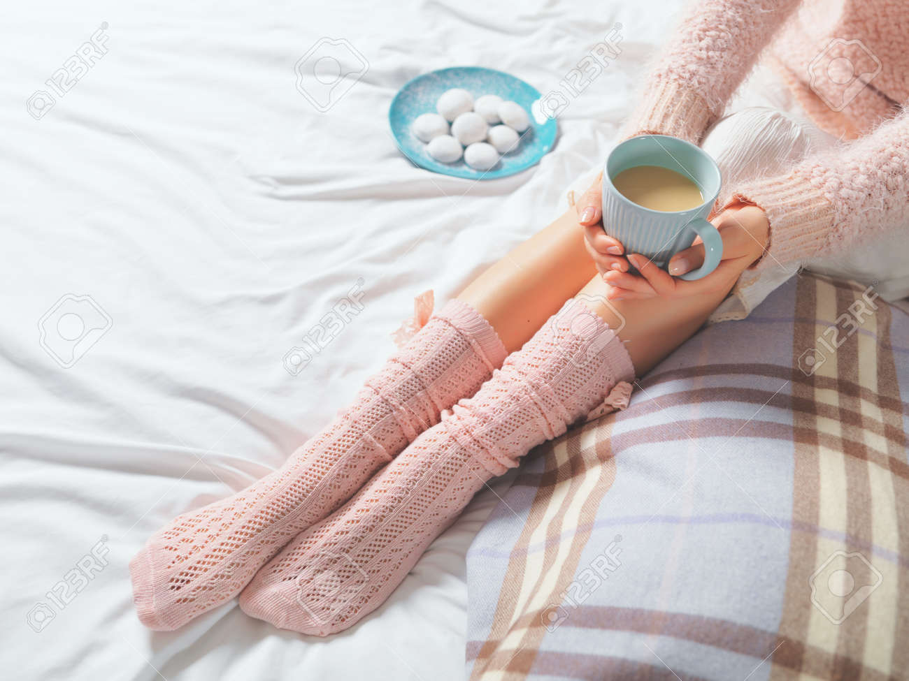 Woman relaxing at cozy home atmosphere on the bed. Young woman with cup of coffee or cocoa in hands and cookies enjoying comfort. Soft light and comfy lifestyle concept. - 41581627