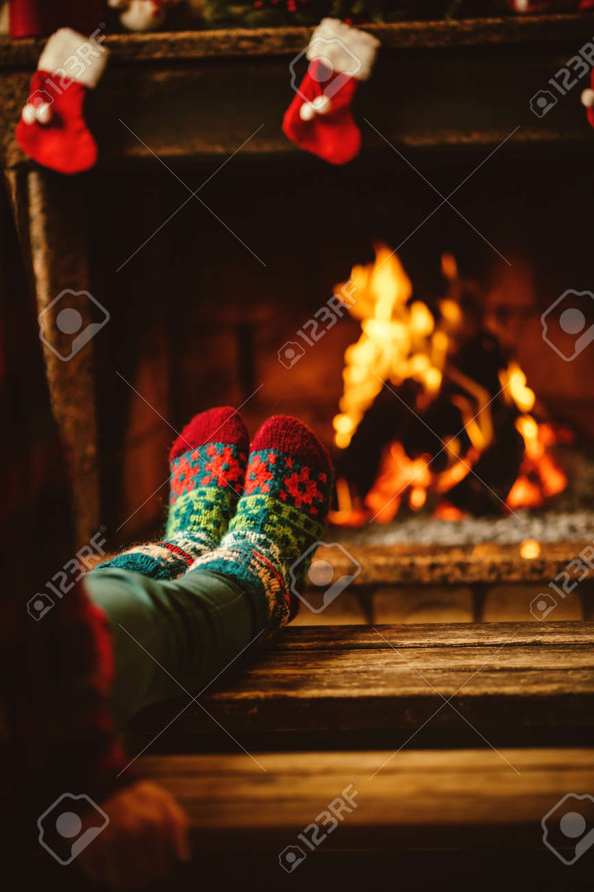 Feet in woollen socks by the fireplace. Woman relaxes by warm fire and warming up her feet in woollen socks. Close up on feet. Winter and Christmas holidays concept. - 46927044