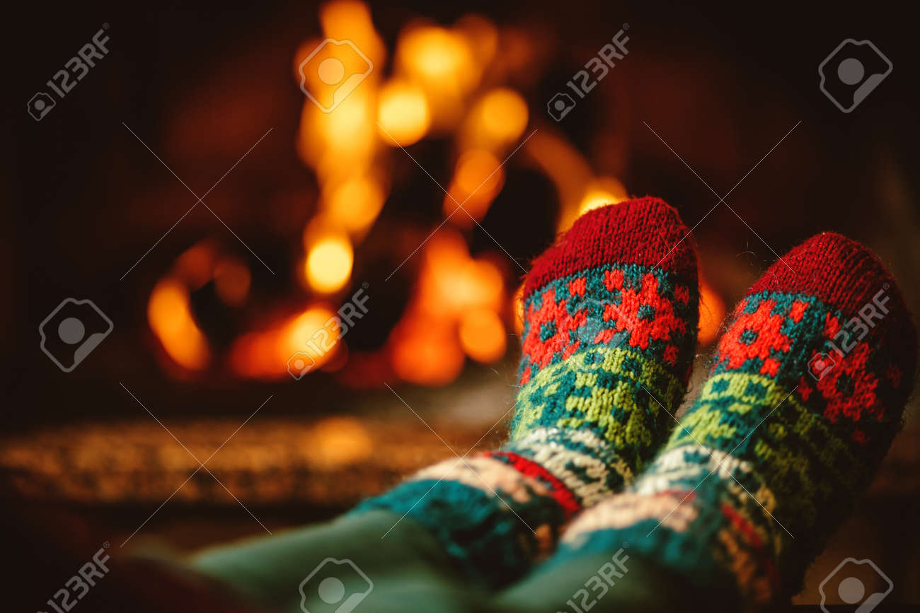 feet in woollen socks by the fireplace woman relaxes by warm