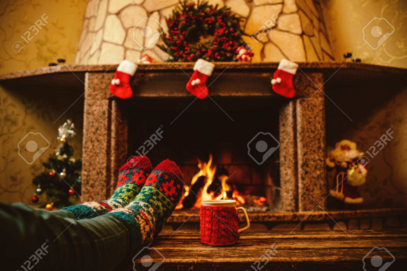 Feet in woollen socks by the Christmas fireplace. Woman relaxes by warm fire with a cup of hot drink and warming up her feet in woollen socks. Close up on feet. Winter and Christmas holidays concept. - 46927052