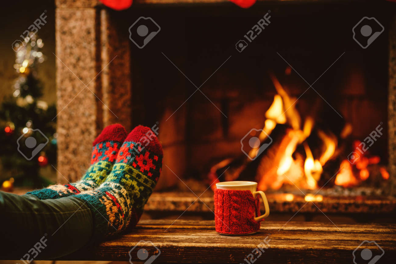 Fireplace Christmas.Feet In Woollen Socks By The Christmas Fireplace Woman Relaxes