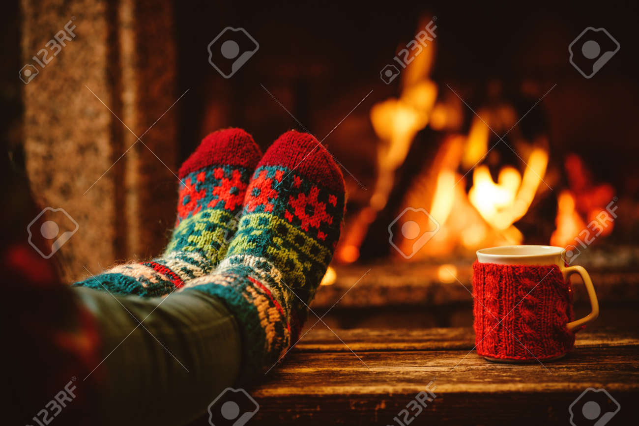 Feet in woollen socks by the Christmas fireplace. Woman relaxes by warm fire with a cup of hot drink and warming up her feet in woollen socks. Close up on feet. Winter and Christmas holidays concept. - 46927058