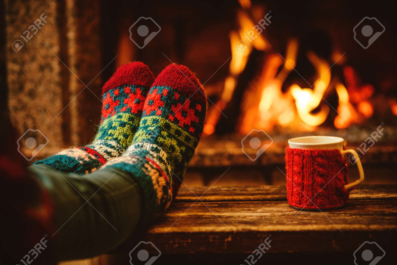 Feet in woollen socks by the Christmas fireplace. Woman relaxes by warm fire with a cup of hot drink and warming up her feet in woollen socks. Close up on feet. Winter and Christmas holidays concept. - 46927059