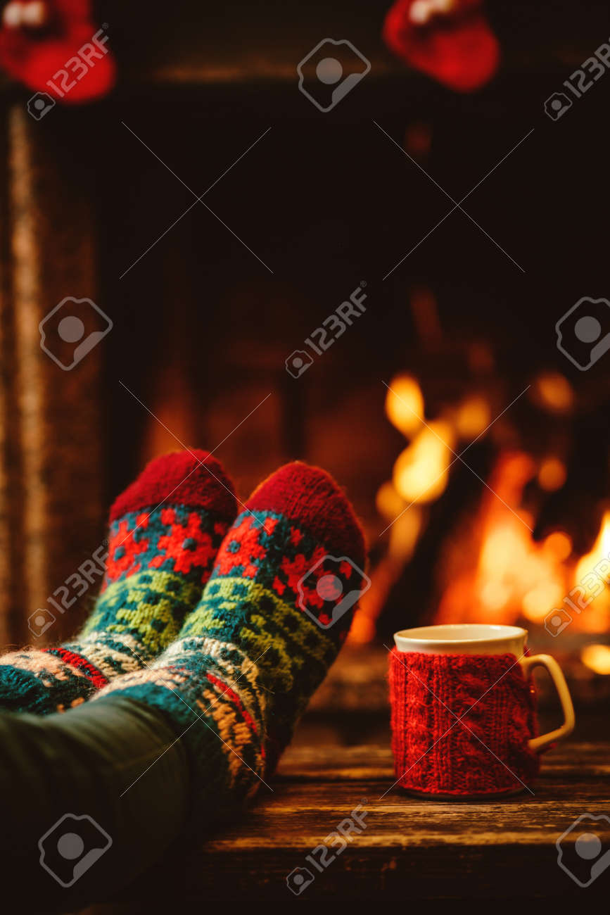 Feet in woollen socks by the Christmas fireplace. Woman relaxes by warm fire with a cup of hot drink and warming up her feet in woollen socks. Close up on feet. Winter and Christmas holidays concept. - 46927060
