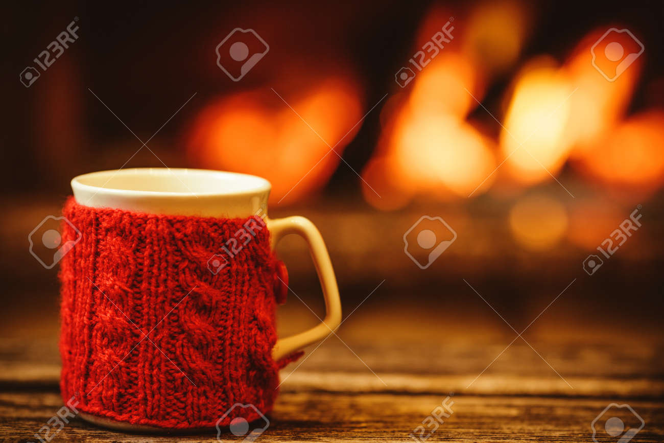 Cup of hot drink in front of warm fireplace. Holiday Christmas concept. Mug in red knitted mitten standing near fireside. Cozy relaxed magical atmosphere in a chalet. - 46927097