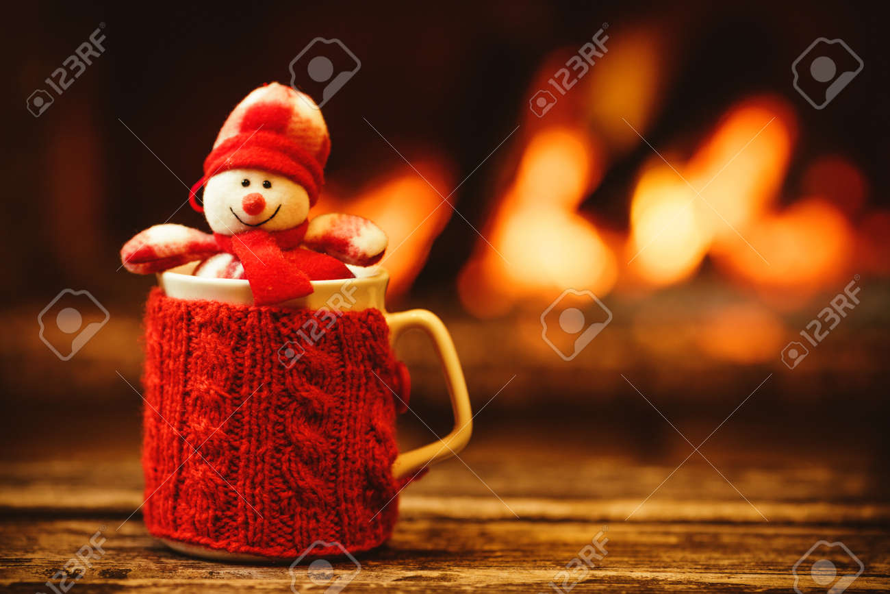 Cup of hot drink in front of warm fireplace. Holiday Christmas concept. Mug in red knitted mitten, decorated with snowman toy, standing near fireside. Cozy relaxed magical atmosphere in a chalet. - 46927099