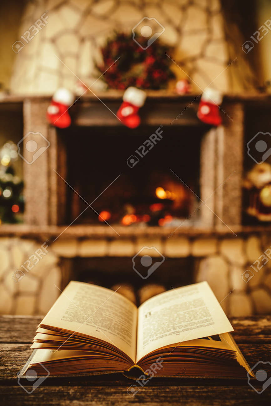 Open book by the Fireplace with Christmas ornaments. Open storybook lying on a wooden bench by the fireside. Cozy relaxed magical atmosphere in a chalet house decorated for Christmas. Holiday concept. - 46927127