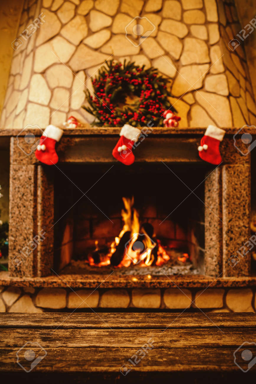 Warm cozy fireplace decorated for Christmas with real wood burning in it. Cozy Christmas concept. Christmas background with space for your text. - 46927167