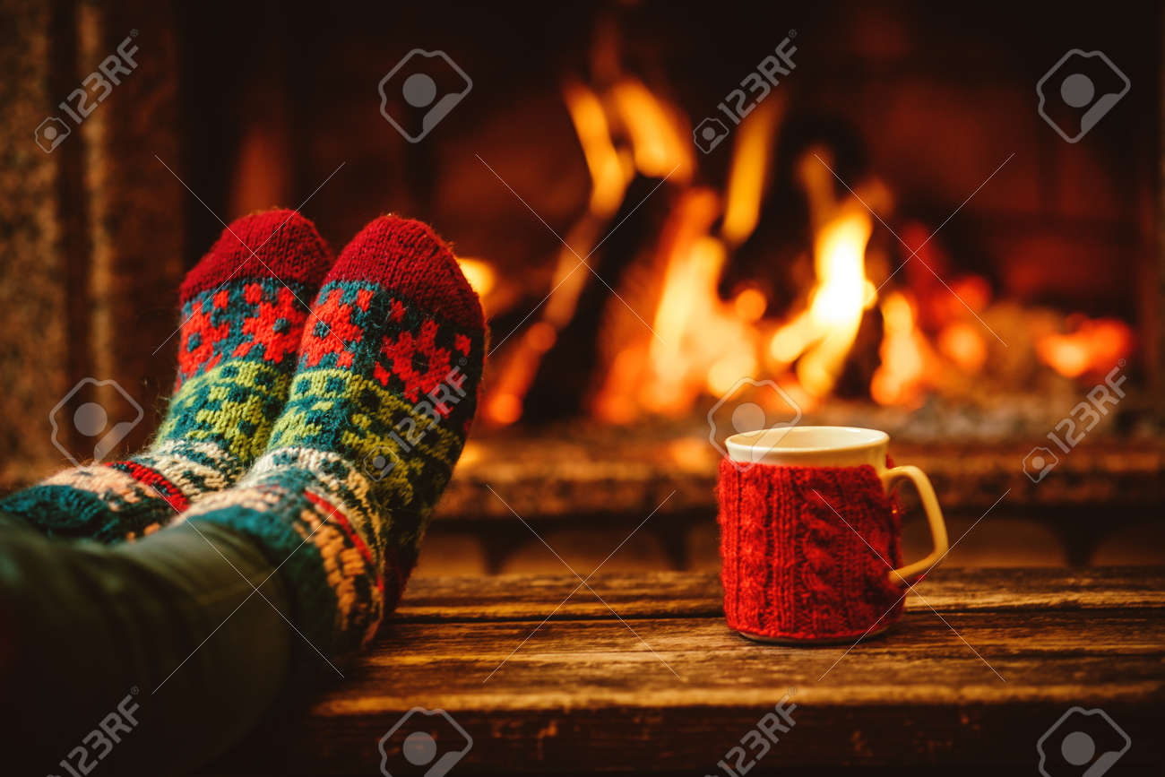 Feet in woollen socks by the Christmas fireplace. Woman relaxes by warm fire with a cup of hot drink and warming up her feet in woollen socks. Close up on feet. Winter and Christmas holidays concept. - 46927175