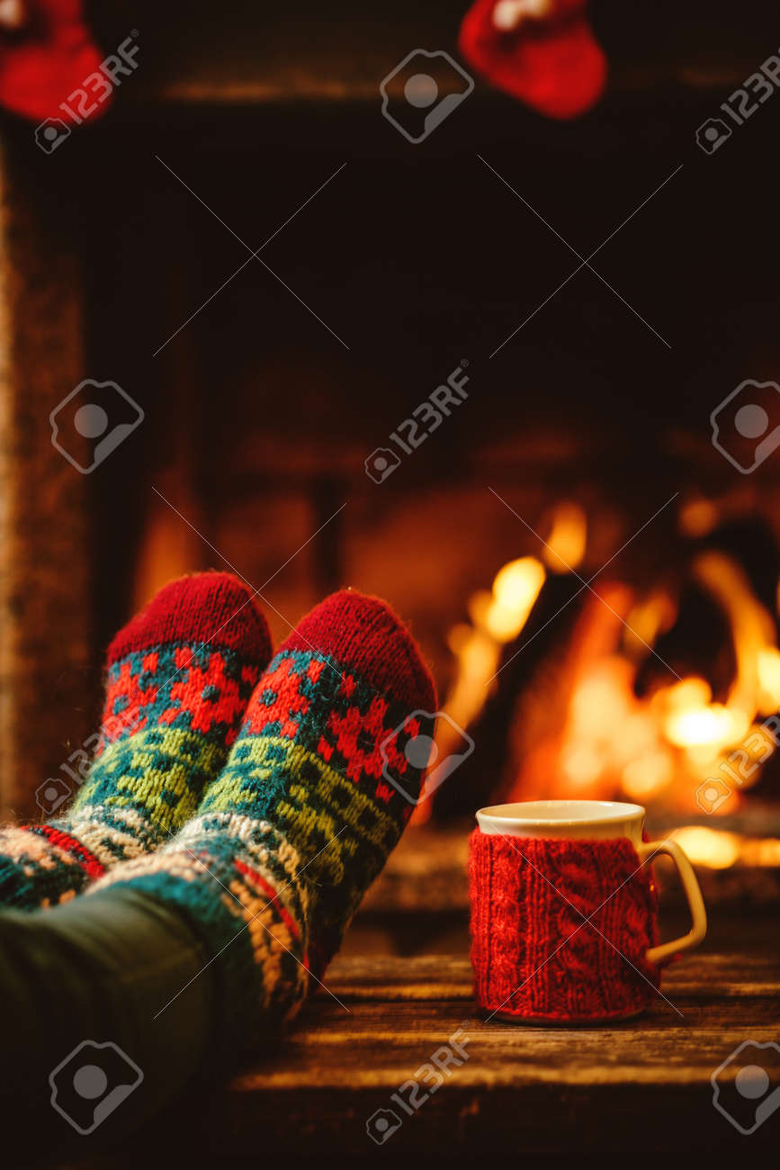 Feet in woollen socks by the Christmas fireplace. Woman relaxes by warm fire with a cup of hot drink and warming up her feet in woollen socks. Close up on feet. Winter and Christmas holidays concept. - 46927176