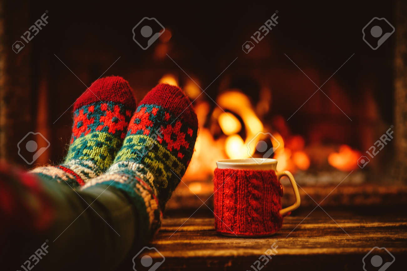 Feet in woollen socks by the Christmas fireplace. Woman relaxes by warm fire with a cup of hot drink and warming up her feet in woollen socks. Close up on feet. Winter and Christmas holidays concept. - 46927179