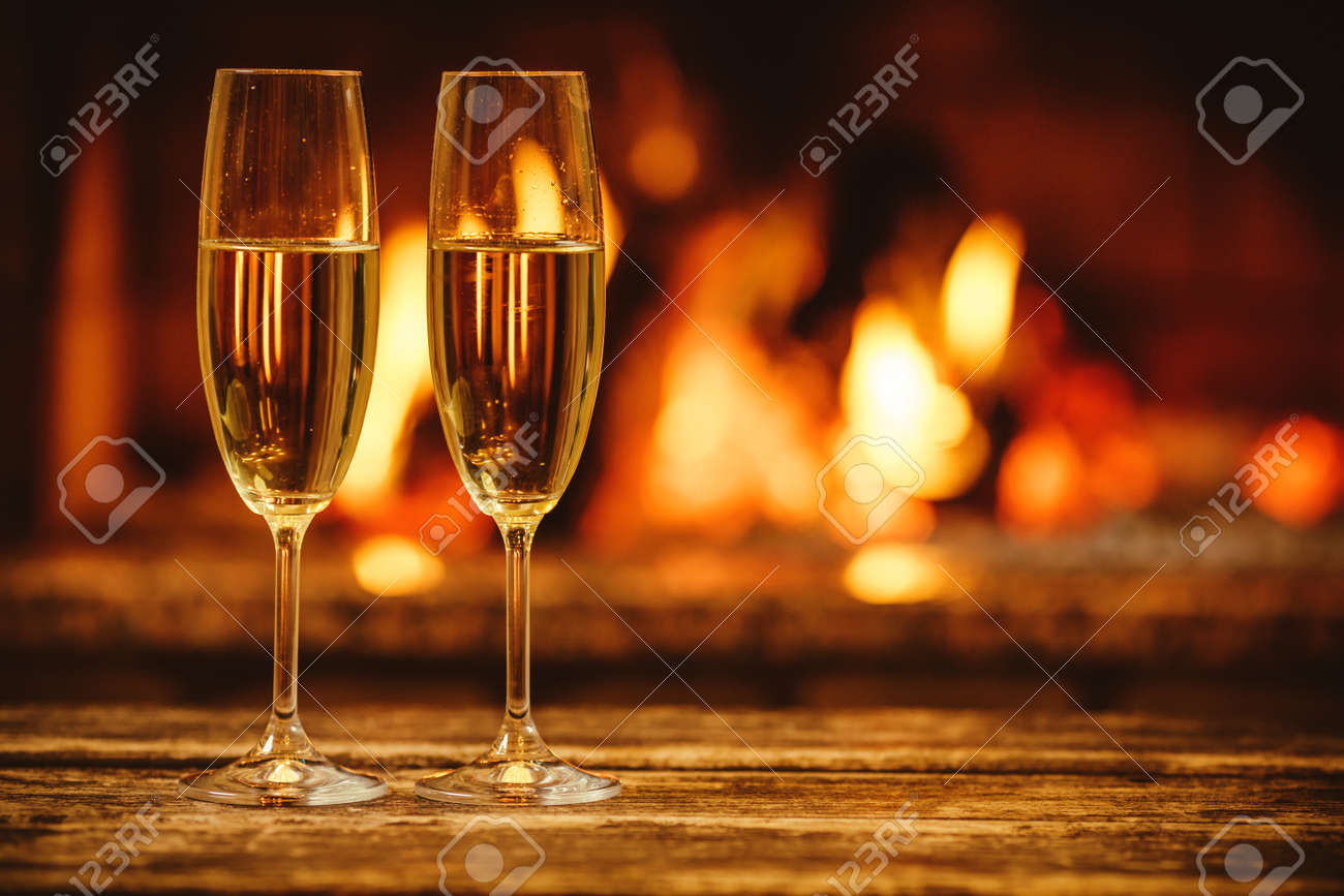 Two glasses of sparkling champagne in front of warm fireplace. Cozy relaxed magical atmosphere in a chalet house by the fireside. Snug holiday concept. Beautiful background with shimmering wine. - 46927181
