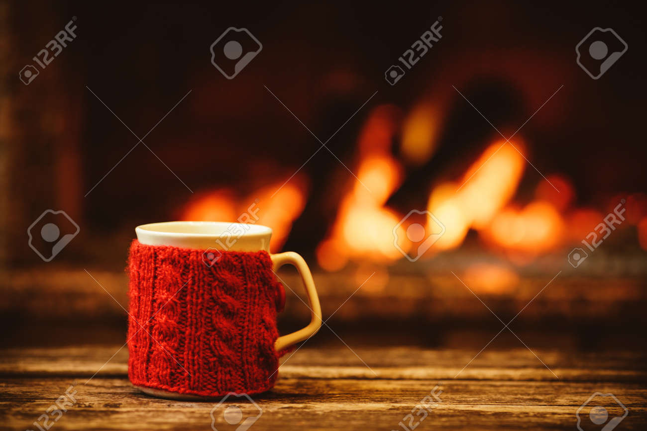 Cup of hot drink in front of warm fireplace. Holiday Christmas concept. Mug in red knitted mitten standing near fireside. Cozy relaxed magical atmosphere in a chalet. - 46927186