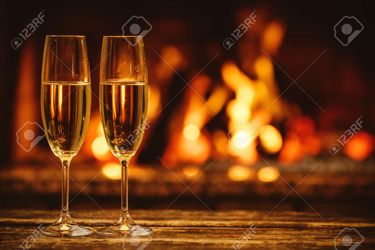Two glasses of sparkling champagne in front of warm fireplace. Cozy relaxed magical atmosphere in a chalet house by the fireside. Snug holiday concept. Beautiful background with shimmering wine. - 46927187