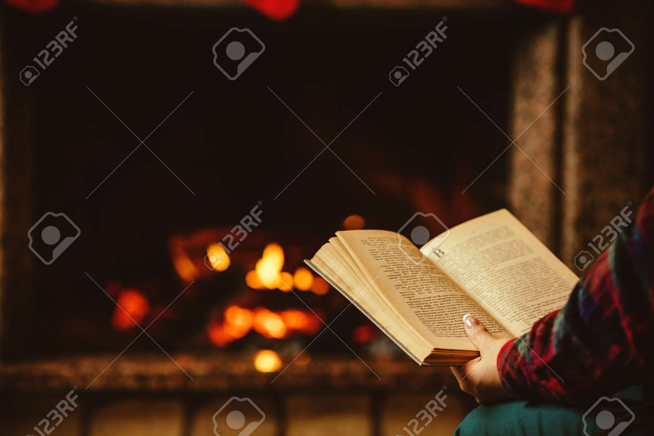 Woman reading a book by the fireplace. Young woman reading a book by the warm fireplace decorated for Christmas. Relaxed holiday evening concept. - 46927144