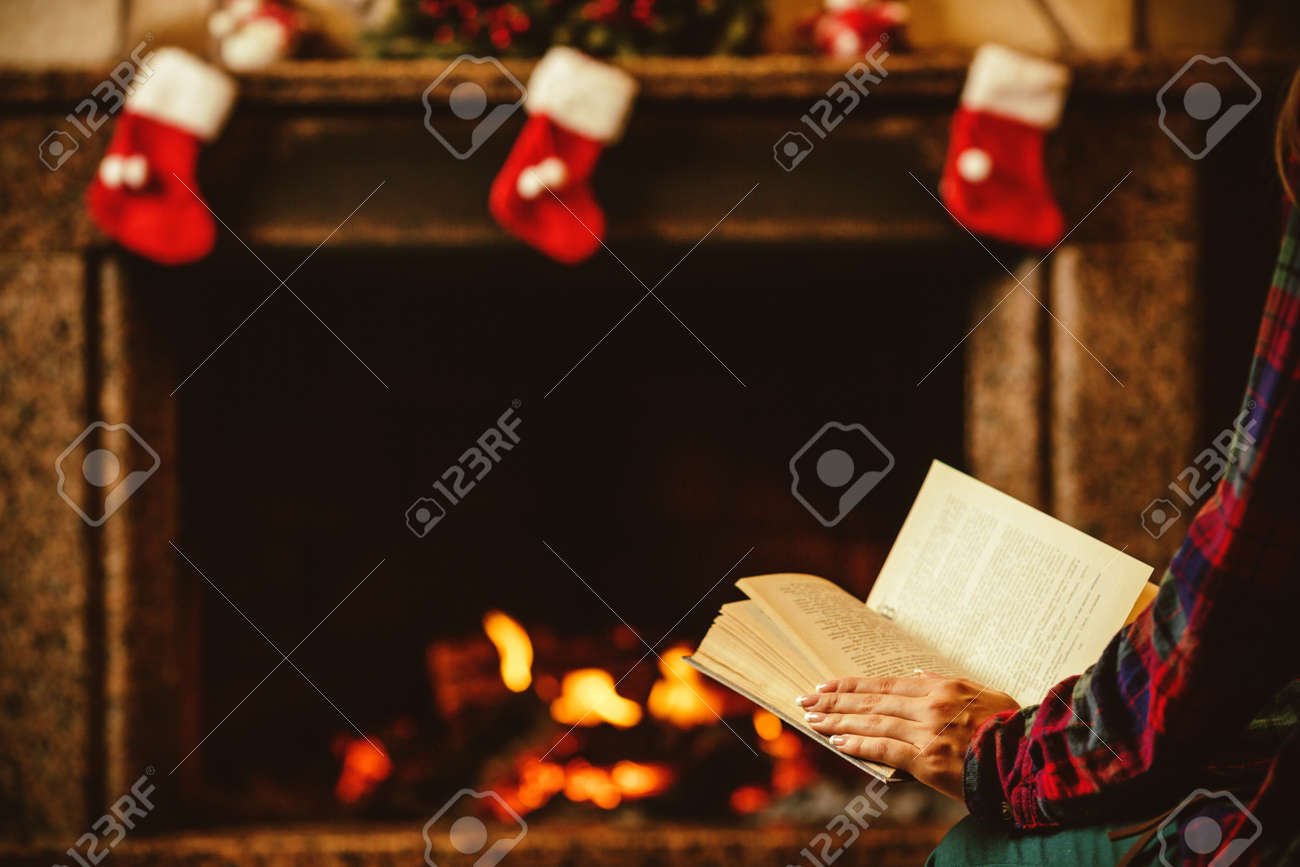 Woman reading a book by the fireplace. Young woman reading a book by the warm fireplace decorated for Christmas. Relaxed holiday evening concept. - 46927063