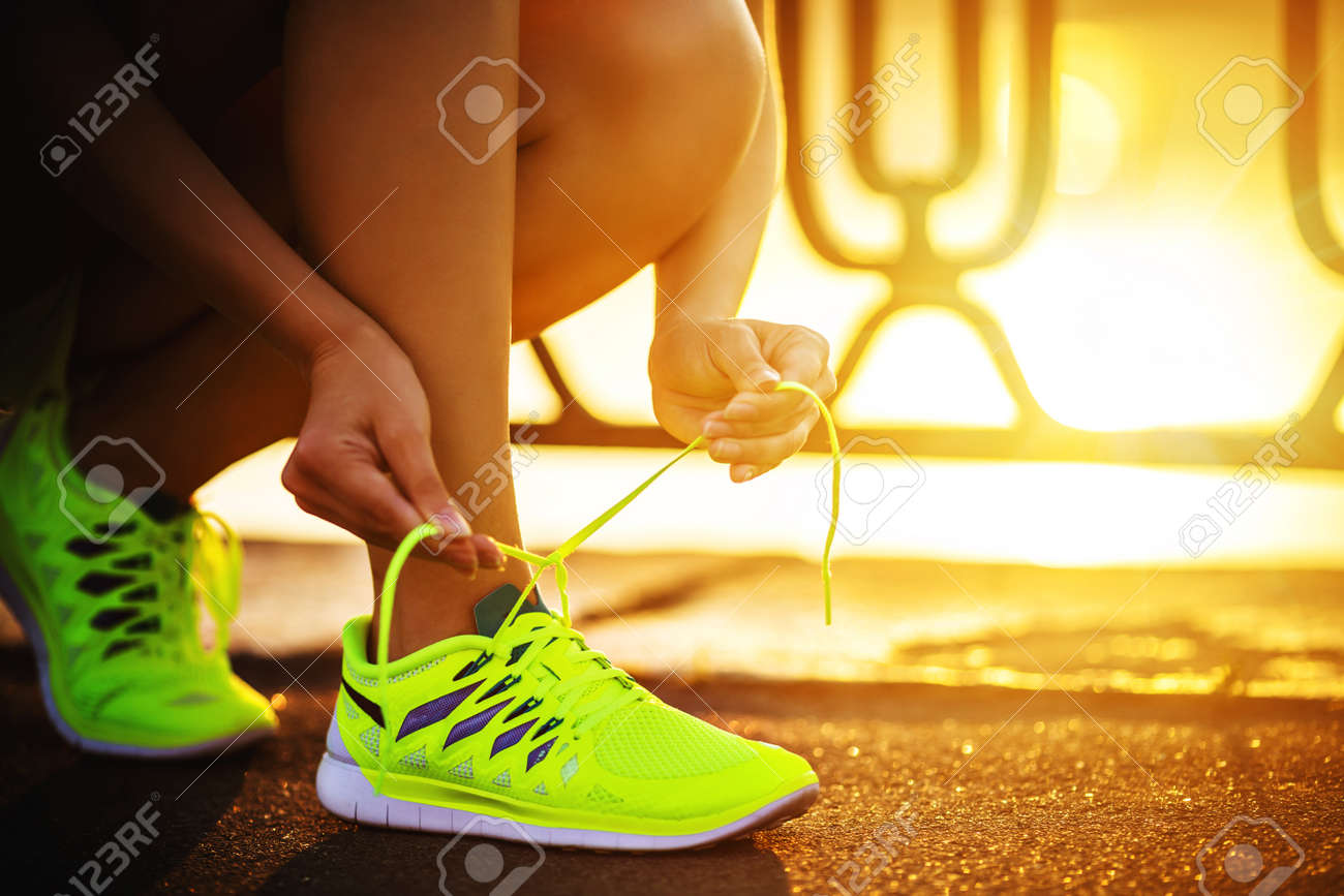 Running shoes. Barefoot running shoes closeup. Female athlete tying laces for jogging on road in minimalistic barefoot running shoes. Runner getting ready for training. Sport lifestyle. - 47987133