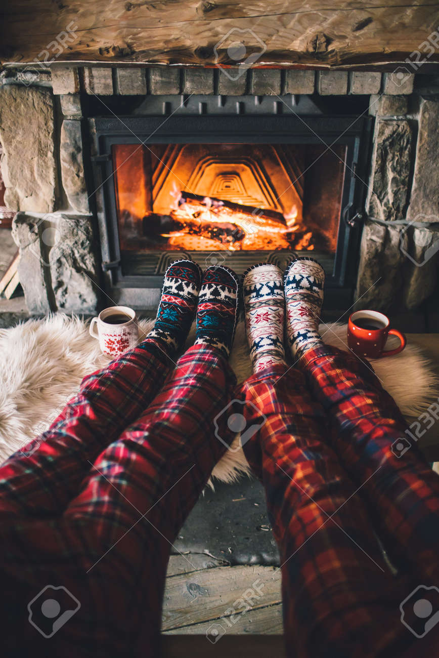 Couple sitting under the blanket, relaxes by warm fire and warming up their feet in woolen socks. - 58947458