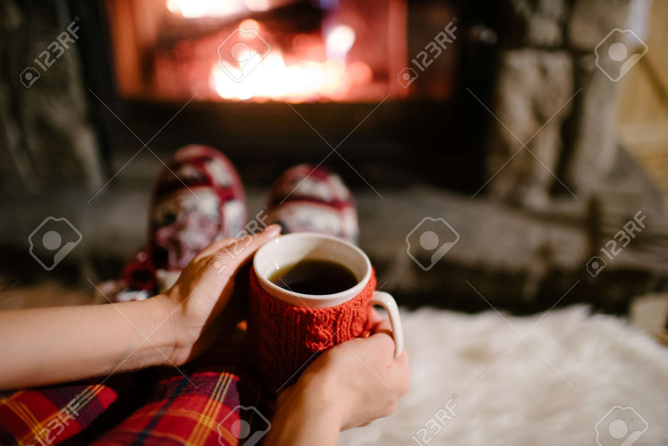 woman holding a cup of tea by the christmas fireplace woman