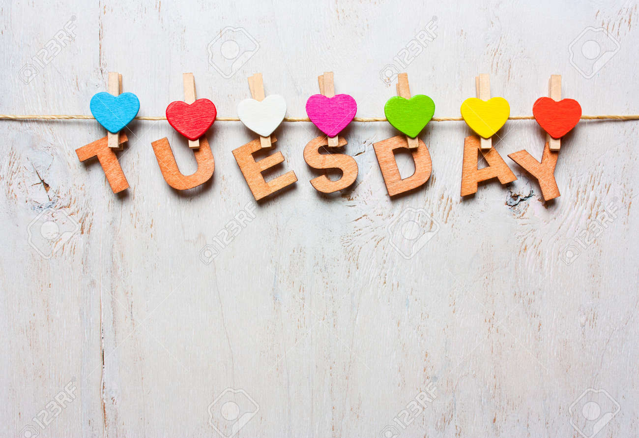 stock photo word tuesday from wooden letters with colored clothespins on a white wooden background