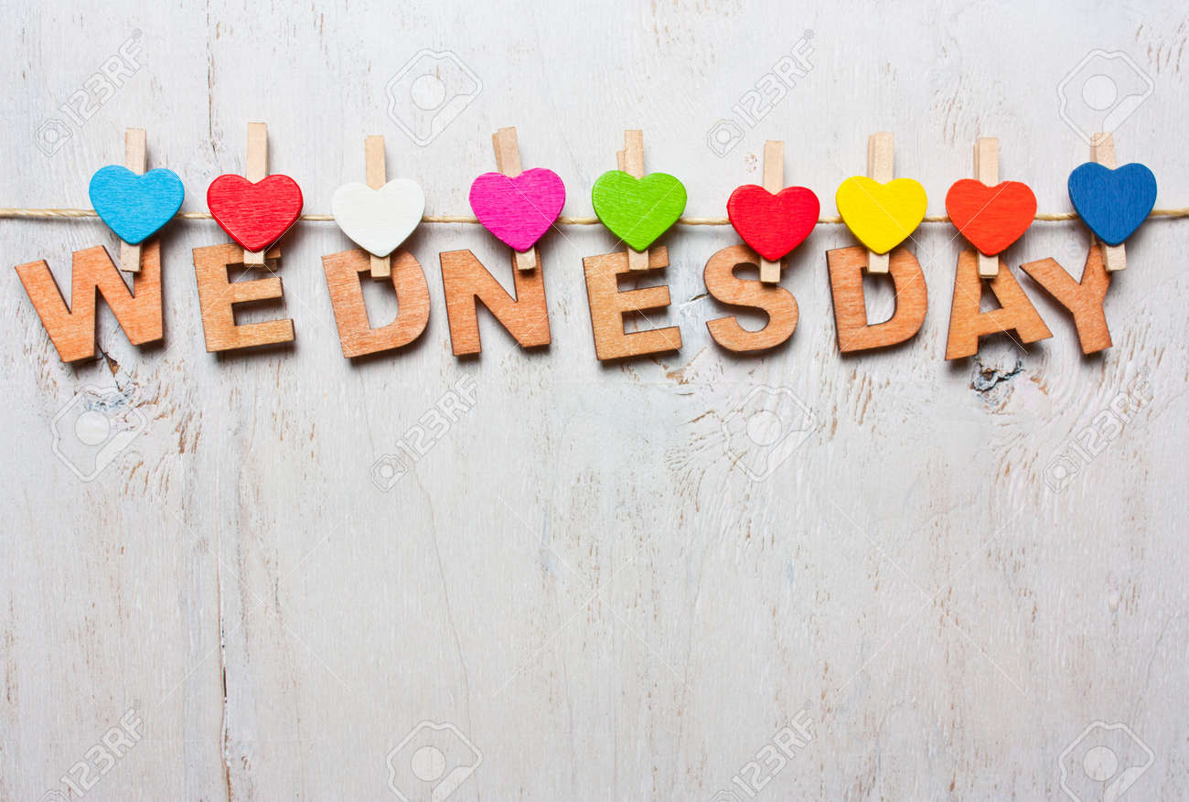 stock photo wednesday word from wooden letters with colored clothespins on a white wooden background