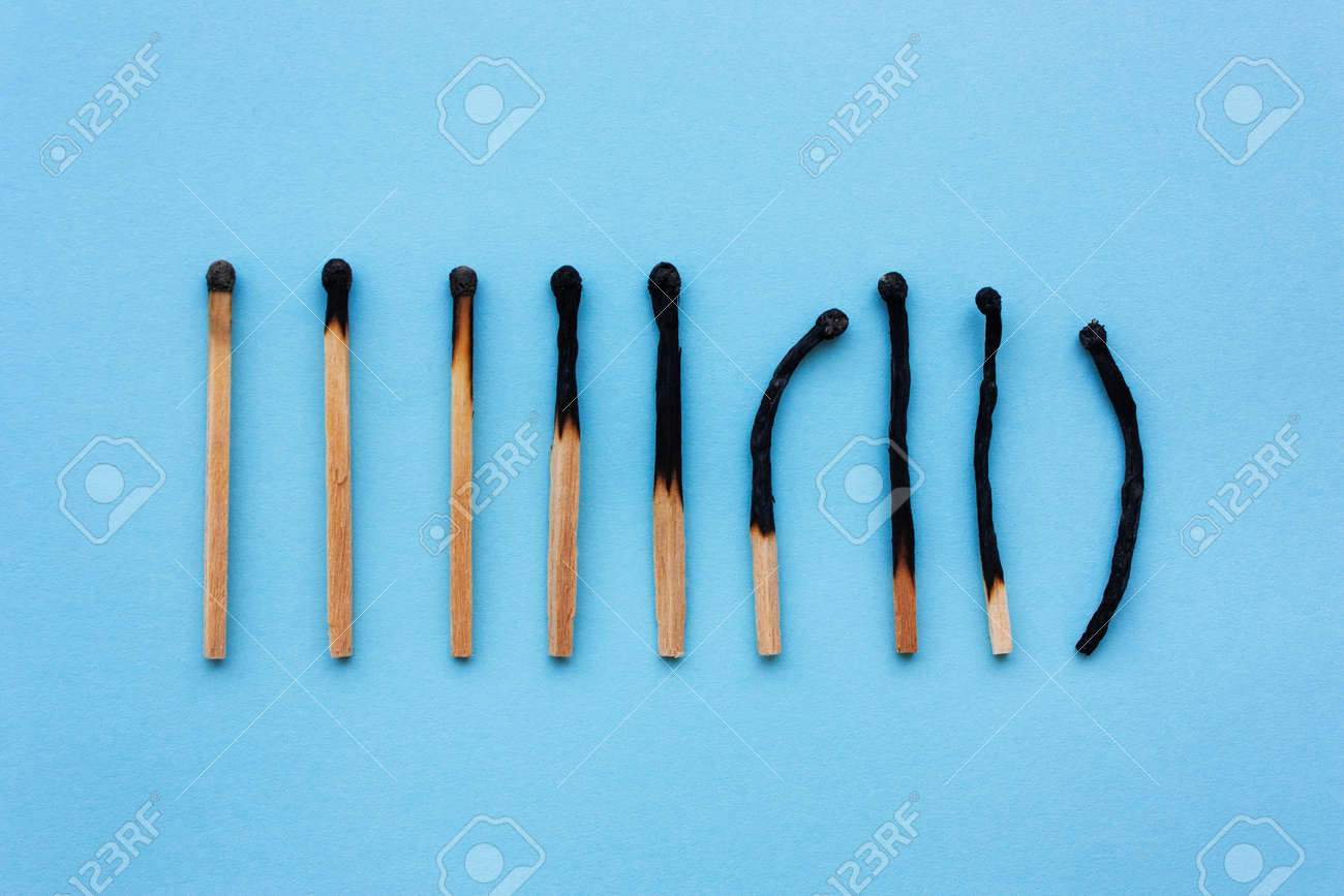 Burned matches in a row on a blue background. The concept of depression, extinction, illness, burnout, aging. View from above, flat - 104942831