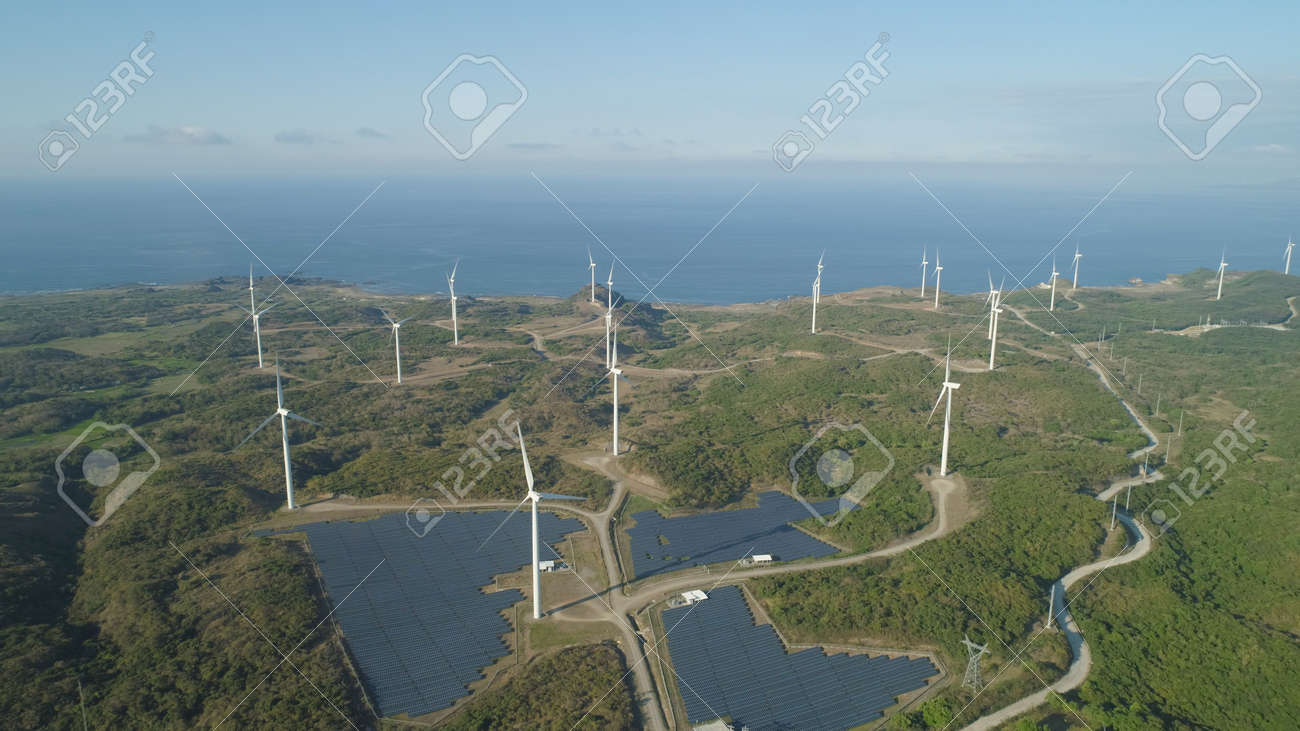Aerial view of Windmills for electric power production on the seashore. Bangui Windmills in Ilocos Norte, Philippines. Solar farm, Solar power station. Ecological landscape: Windmills, sea, mountains. Pagudpud. - 115627367
