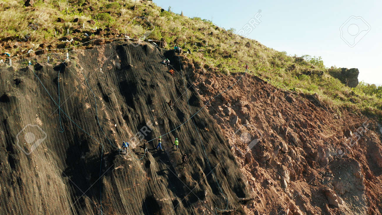 Protection of road from mountain slough, rockfall with metal accumulative restraining net fences. Workers constructing anti-landslide concrete wall prevent protect against rock slides. Rockfall protection. Workers strengthen the slope of the mountain with steel grid preventing rockfall and landslide on the road. - 160972295