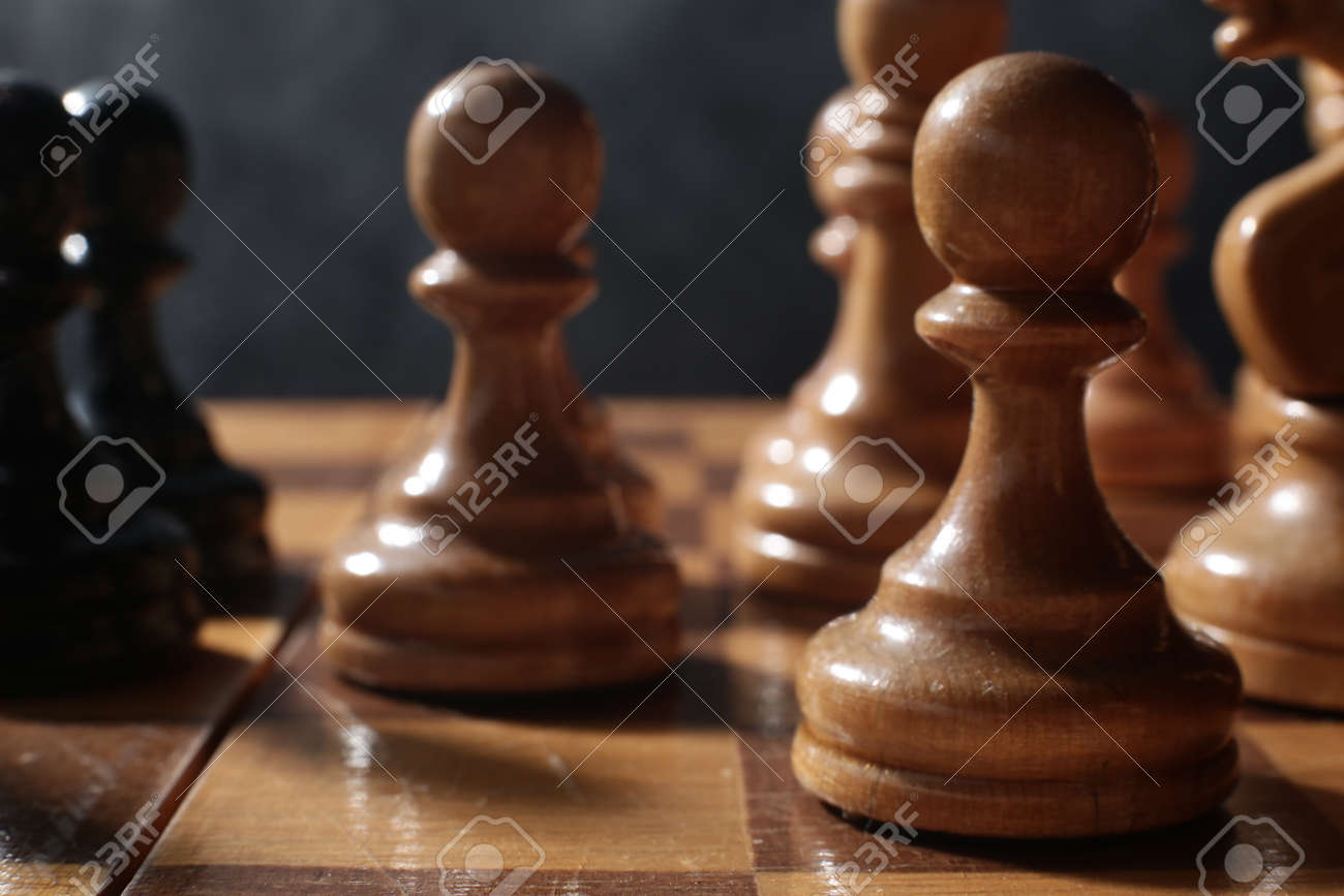 Wooden chess is a board game. Chess pieces on a dark background - 165107286