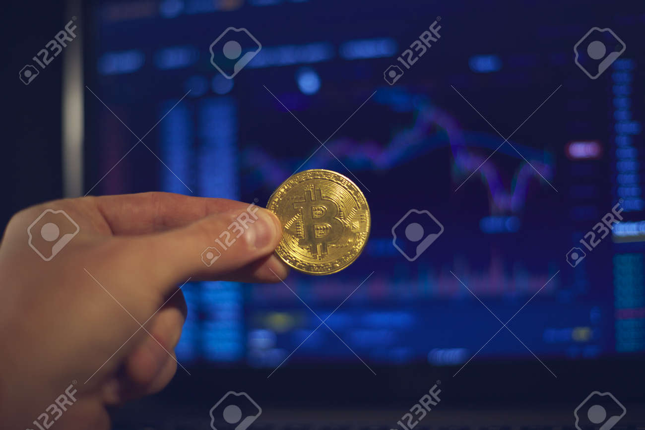 A man holds a gold bitcoin coin in his hand. The graphs of changes in cryptocurrency rates are shown on the laptop monitor - 168659835
