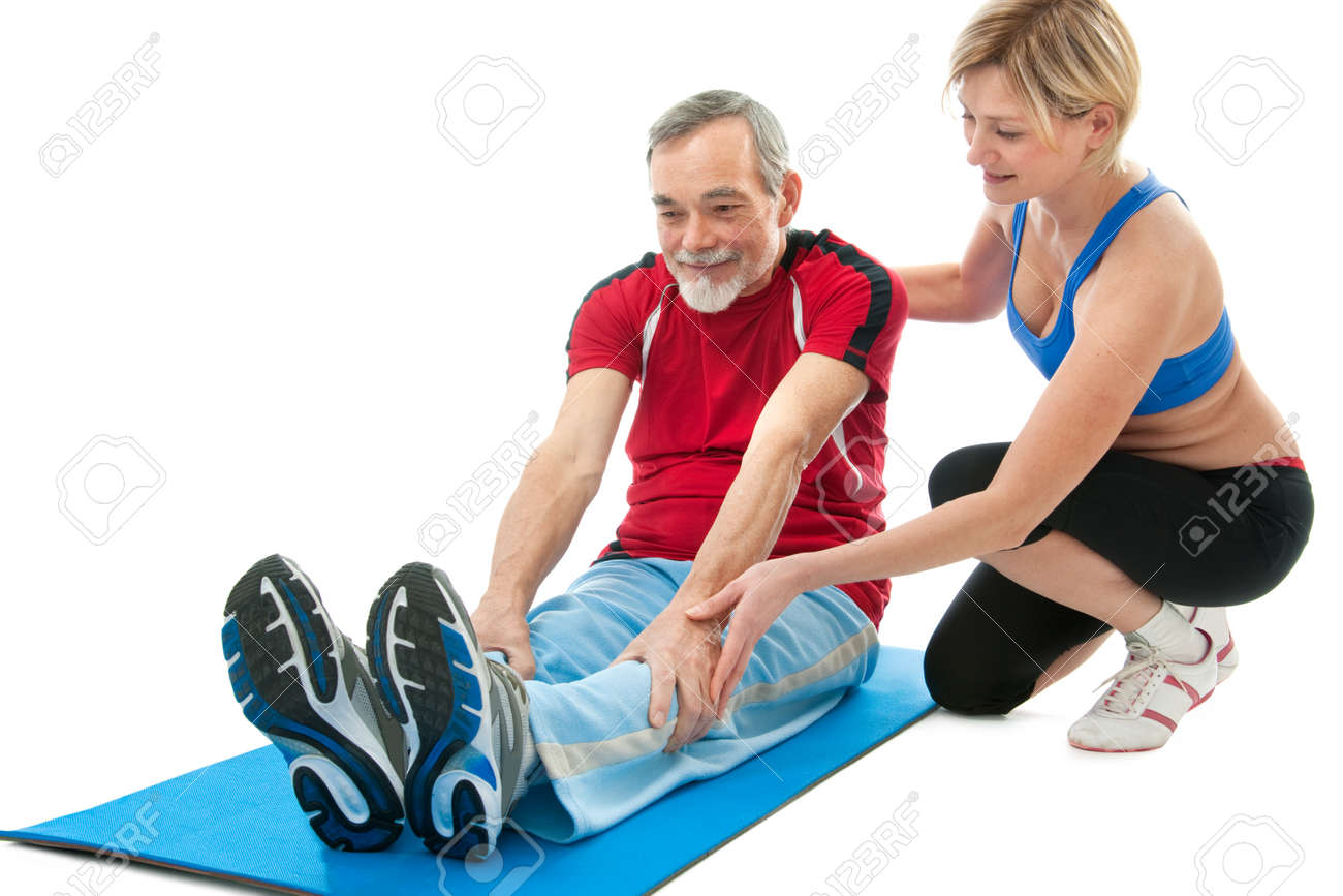 Senior man doing fitness exercise with help of trainer at sport gym Stock Photo - 13336415