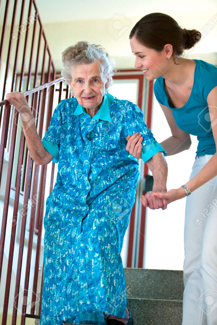 Senior woman is climbing stairs with caregiver Stock Photo - 15202483