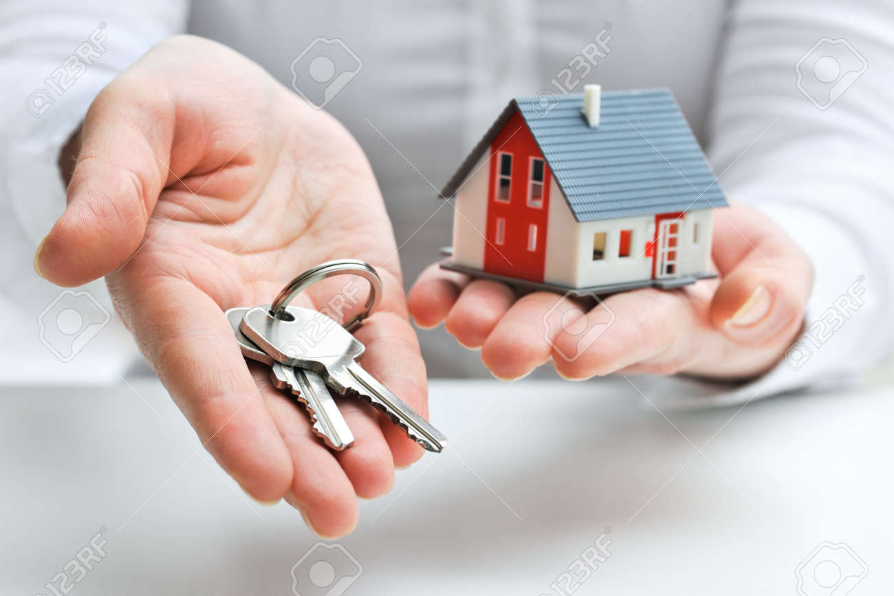Real estate agent with house model and keys Stock Photo - 18148501