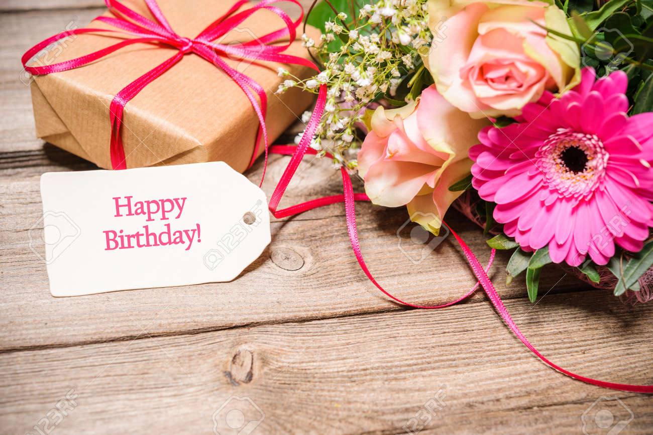 Bunch of flowers and tag with text on wooden background happy bunch of flowers and tag with text on wooden background happy birthday stock photo izmirmasajfo