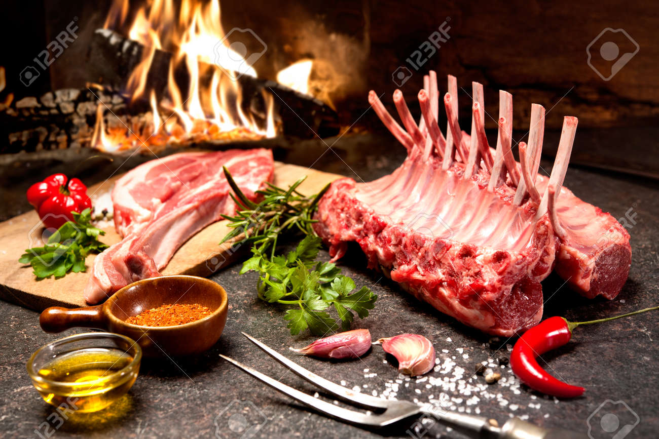 Rack of lamb with seasoning in front of a fireplace - 40694988