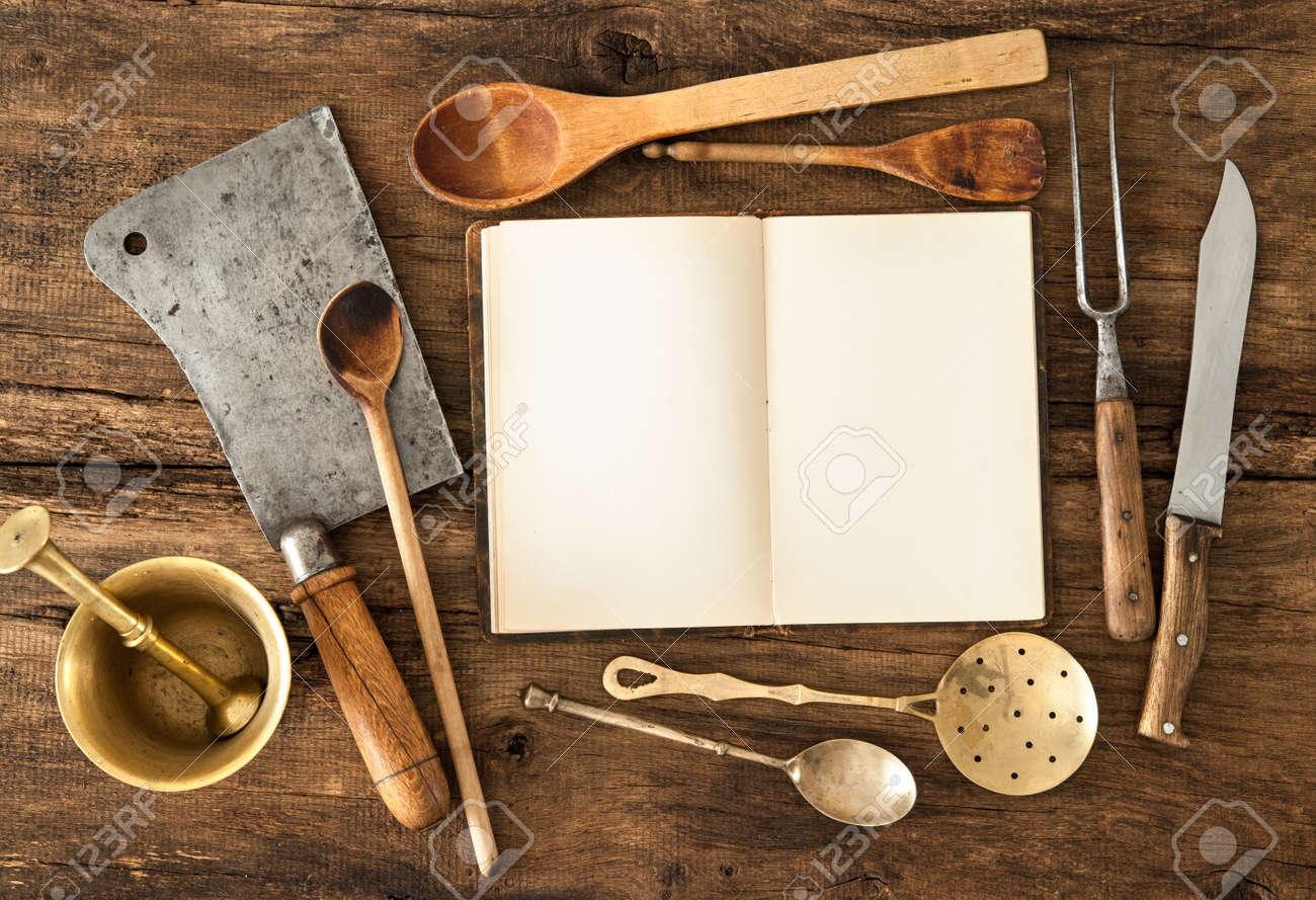 empty notebook or cookbook and vintage kitchen utensils on wooden