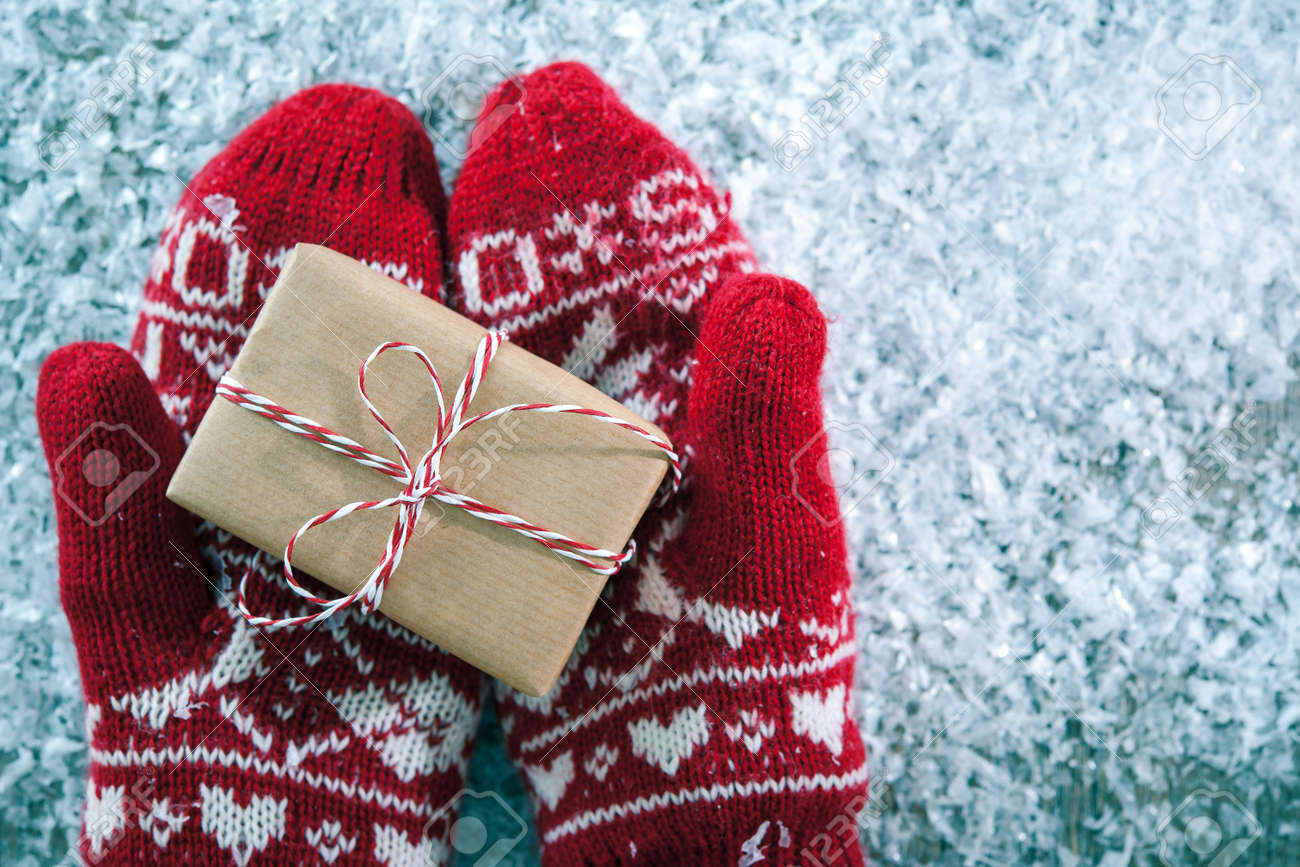 Female hands in winter gloves with christmas gift box - 44129808