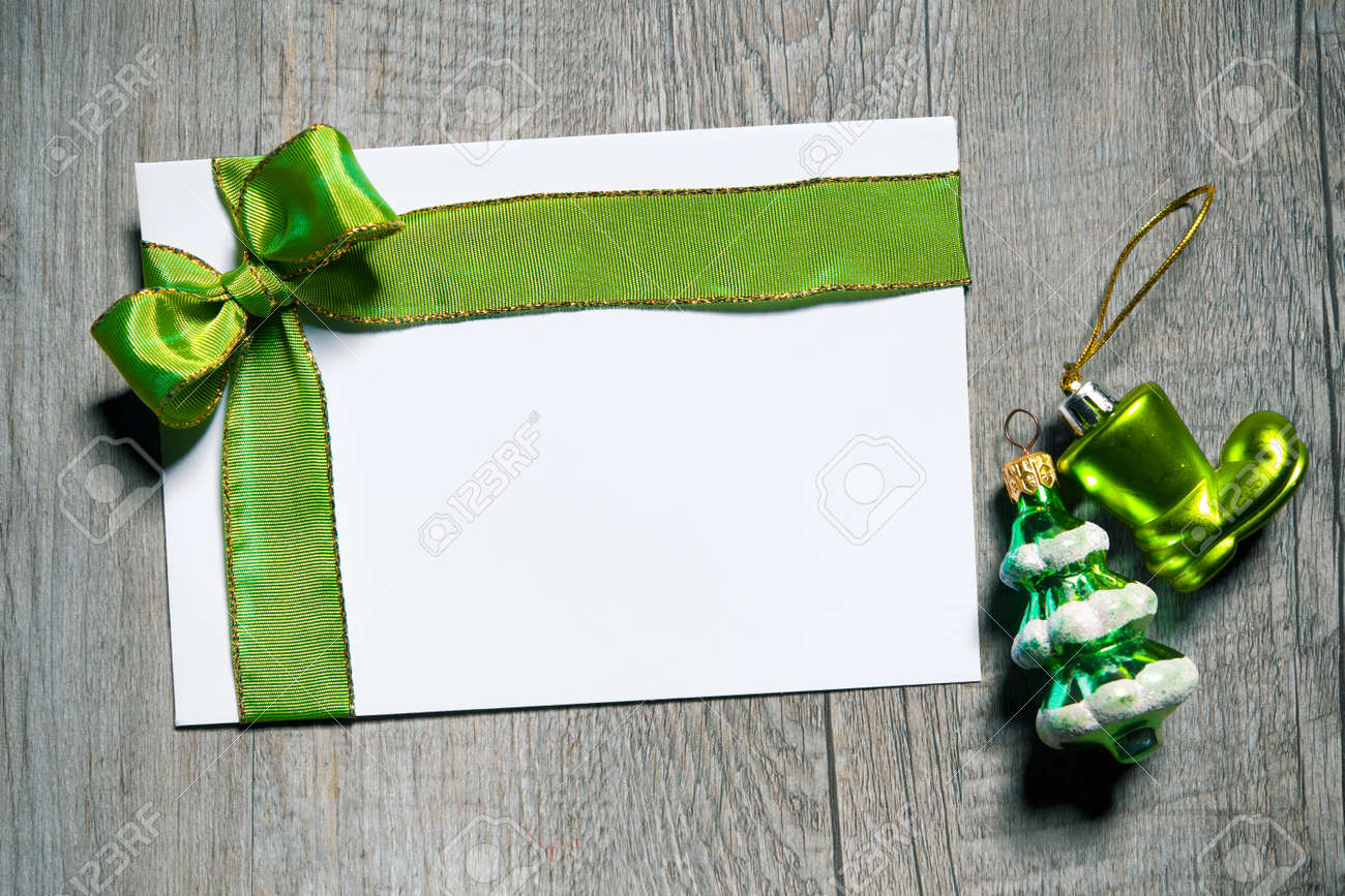 Holidays gift card with green bow on wooden background Stock Photo - 46005236