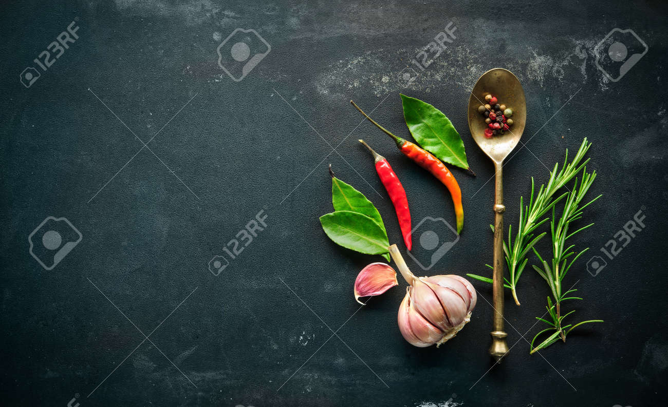Herbs and spices with old metal spoon on slate background Stock Photo - 47115127
