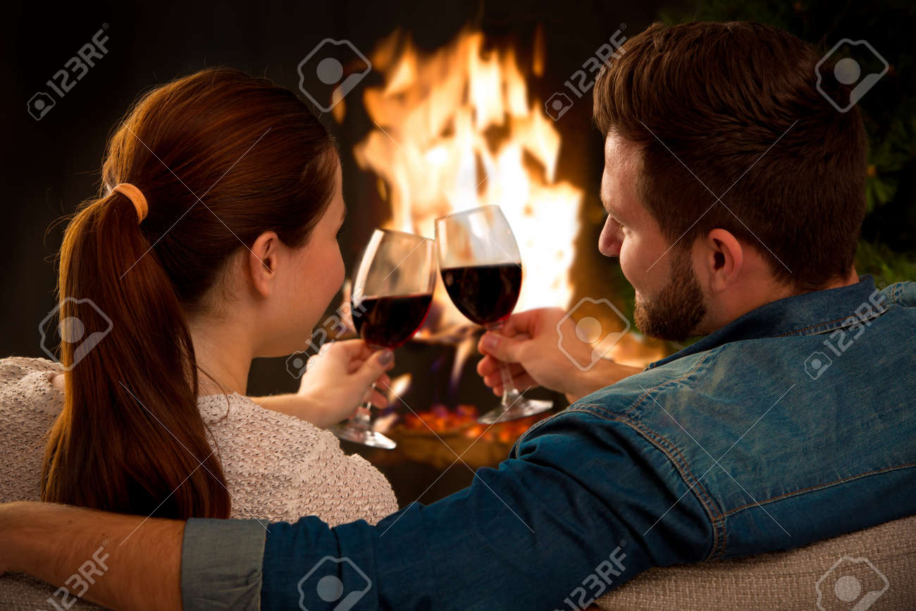 Couple relaxing with glass of wine at romantic fireplace on winter evening Stock Photo - 47631138