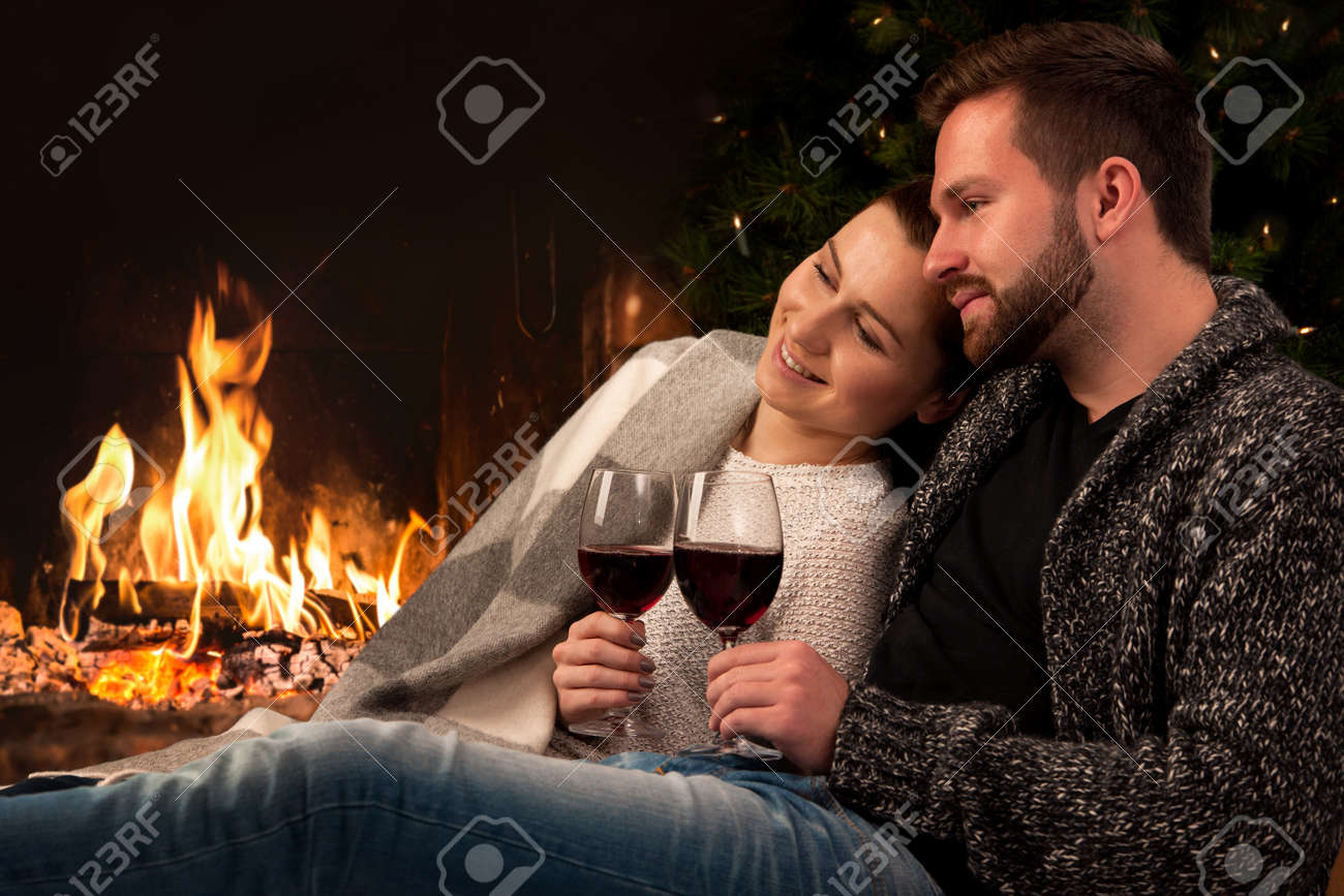 couple relaxing with glass of wine at romantic fireplace on winter